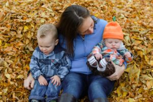 mom and her boys playing in the fall leaves