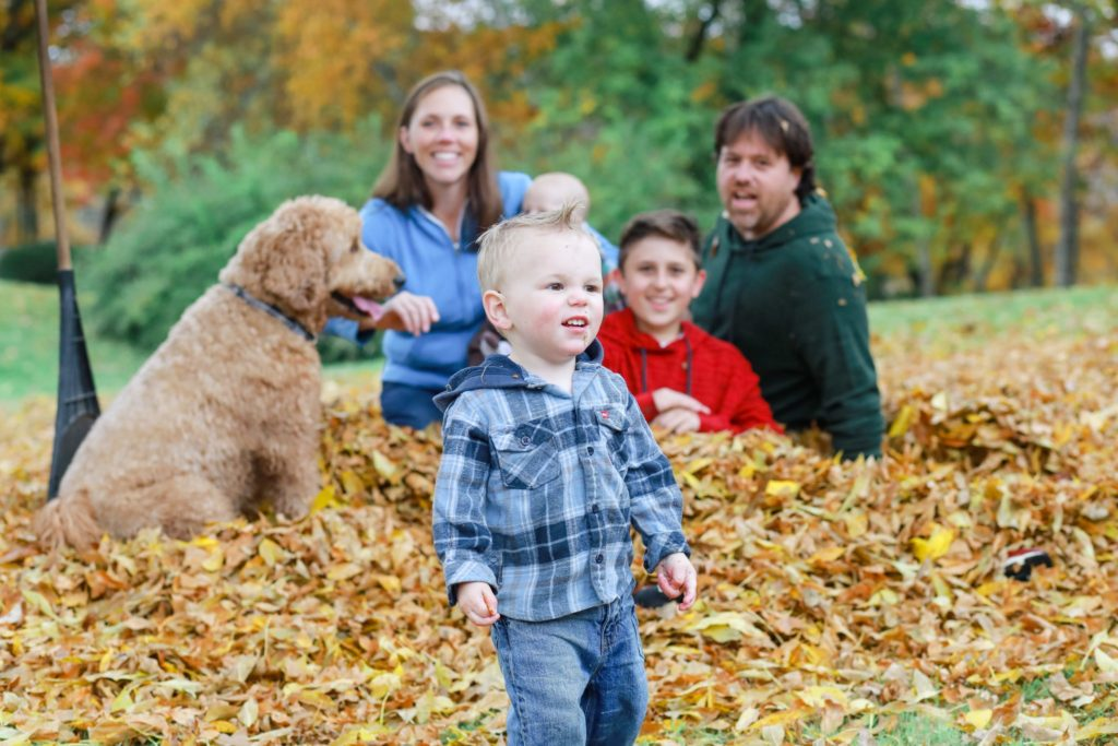 family in the fall leaves with their family dog