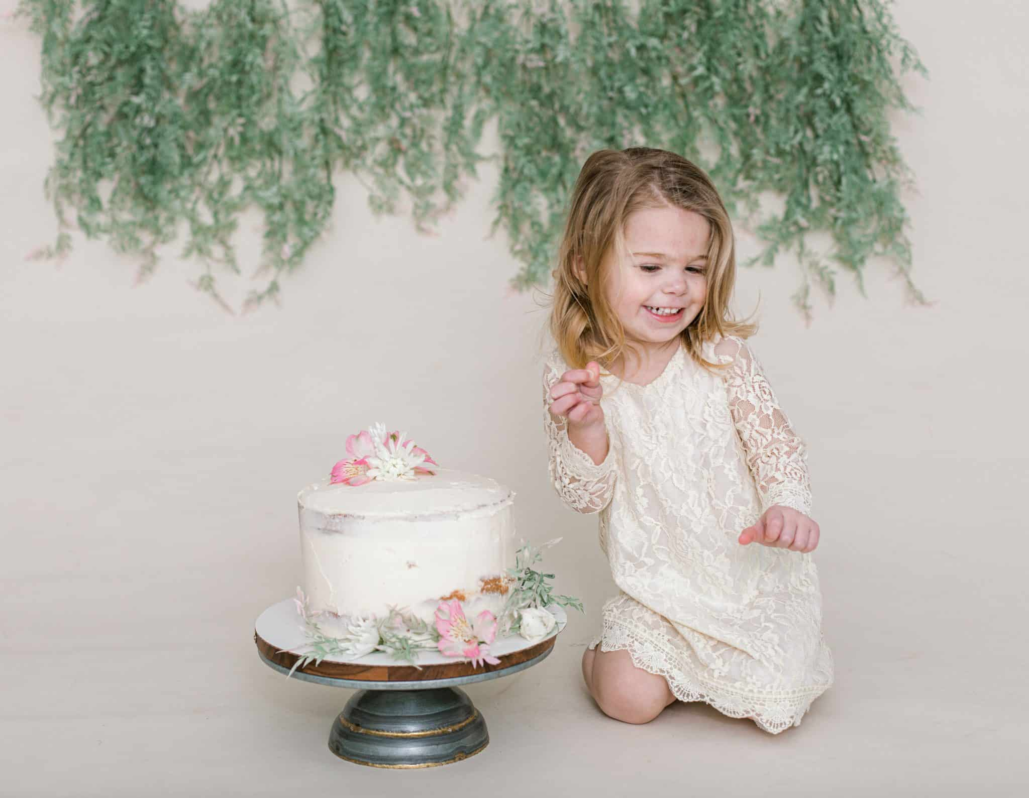 little girl laughing looking down, white cake, green garland, and white dress