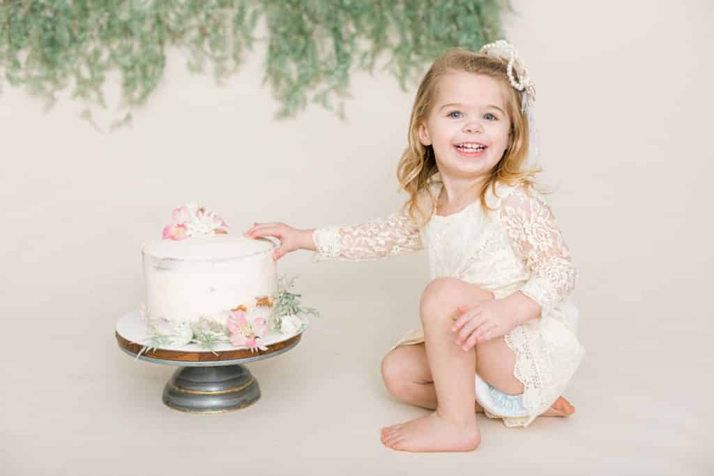 baby girl in a white dress with a botanical themed cake looking at the camera smiling