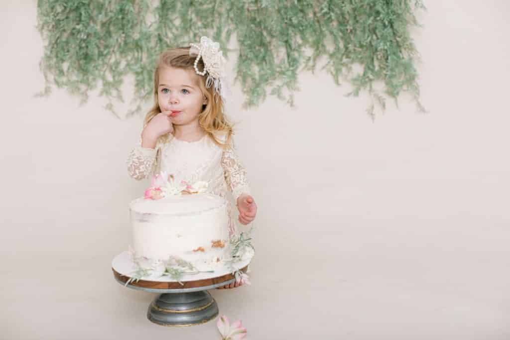 one year old girl in white dress looking at the camera eating cake off her finger