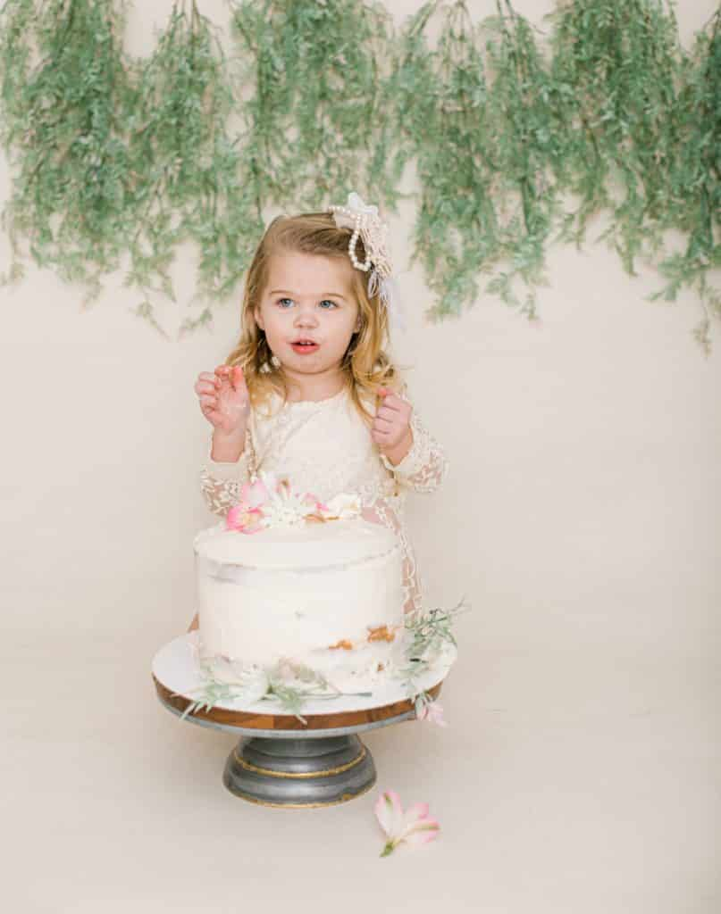 One year old girl looking at the camera with a white cake mouth open