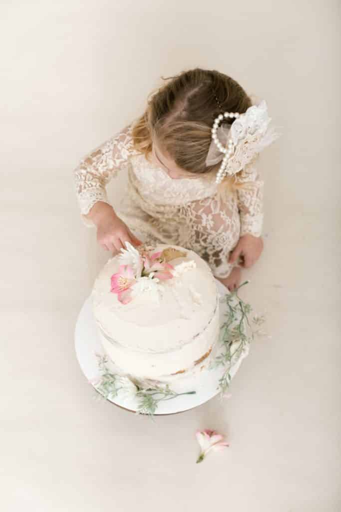 one year old girl looking down at her eaten cake