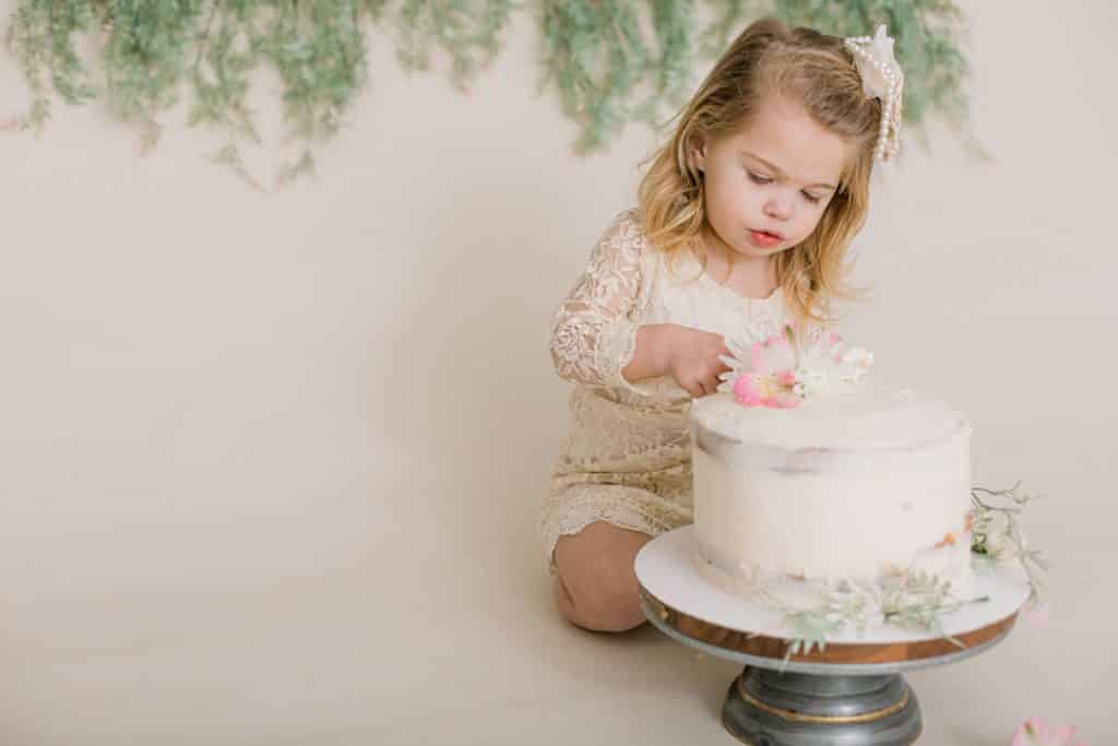 One year old girl looking at and poking her cake