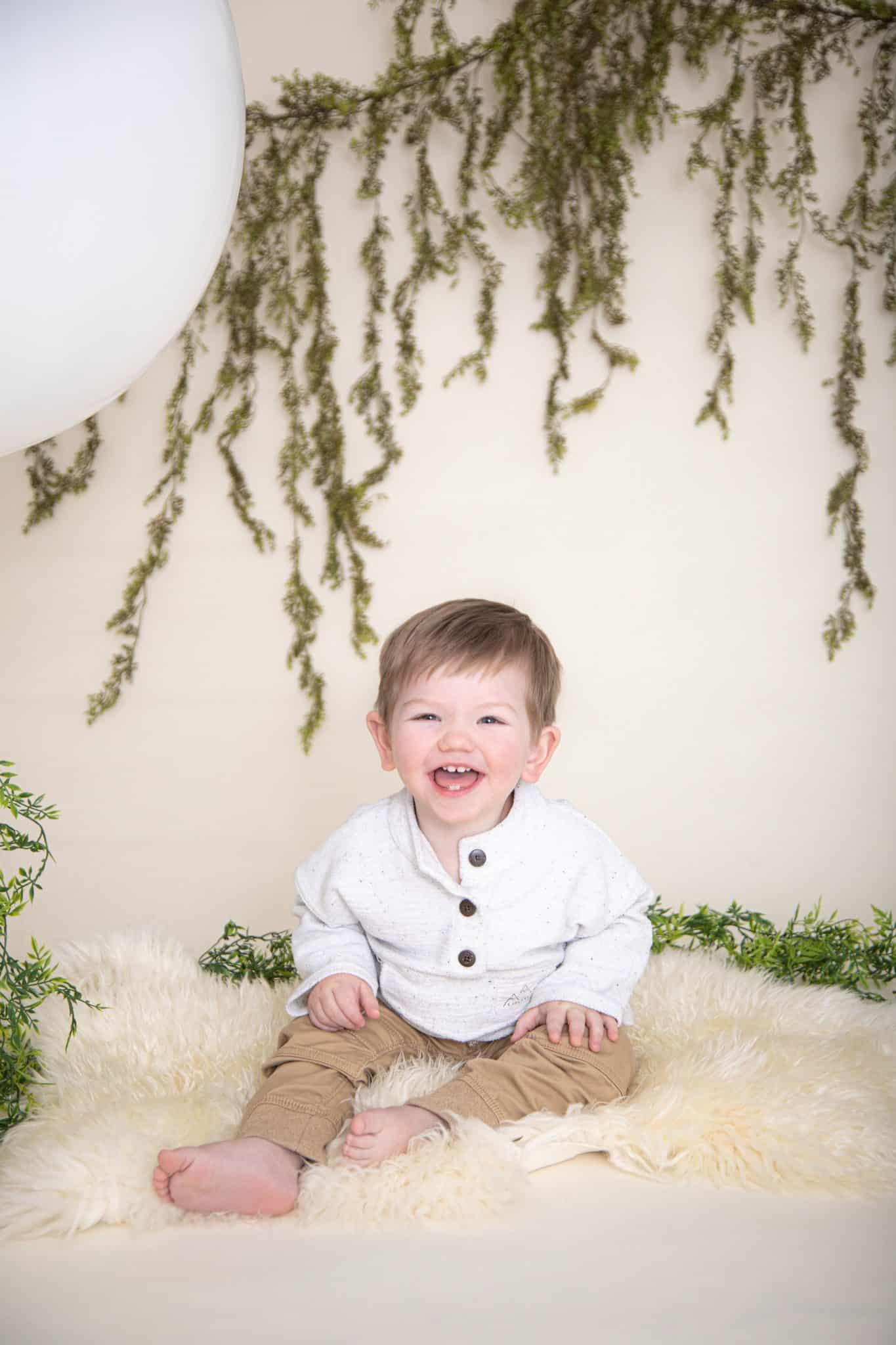 One year boy photos. big white balloon, green garland, white fur