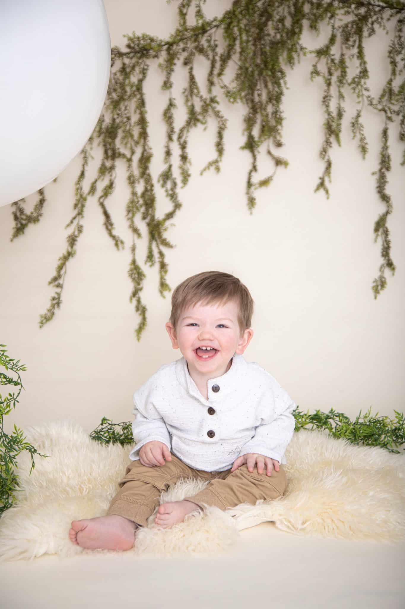 One year boy photos. big white balloon, green garland, white fur