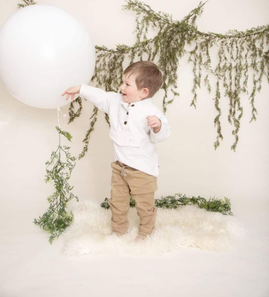 One year old boy in a white sweater and tan pants standing on a white rug, green garland, playing with a large white balloon