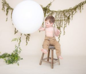 One year photos, large white balloon, baby boy in tan pants, suspenders sitting on a brown stool, with green garland.