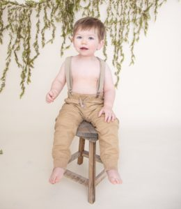 One Year boy sitting on a brown stool wearing suspenders and tan pants, green garland on an off white background.