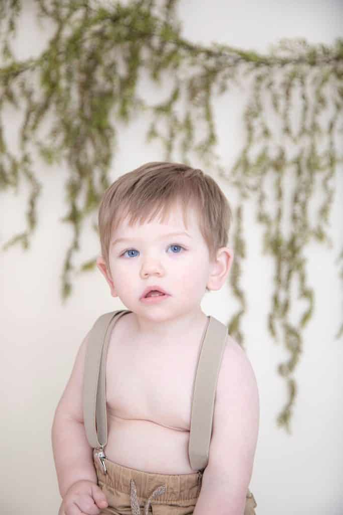 One year boy wearing suspenders with blue eyes, green galrdand