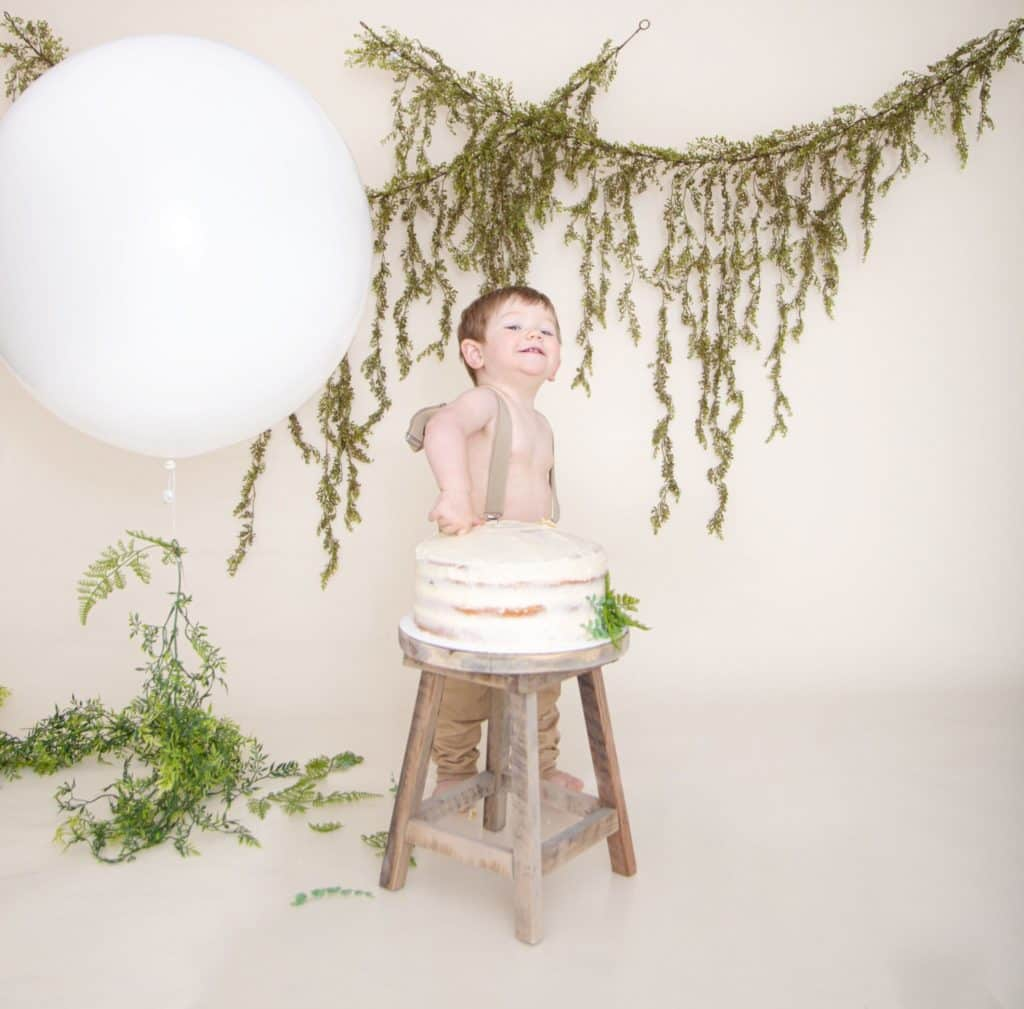 One year cake smash, large white balloon, green garland, off white background, one year old boy in suspenders, and tan pants