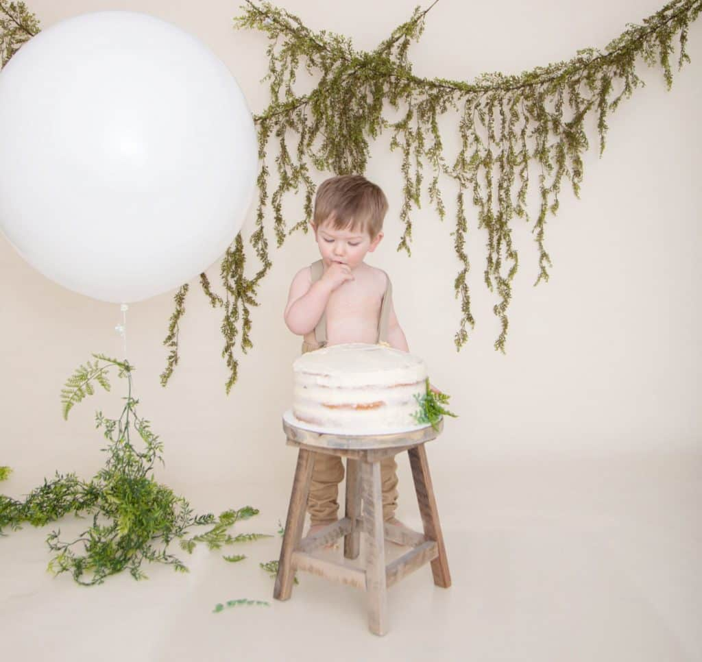 One year old boy in suspenders and tan pants eating a cake, white balloon, green garland, off white background
