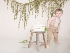 One year old boy in suspenders and tan pants, cake smash, green garland, large white balloon, fur