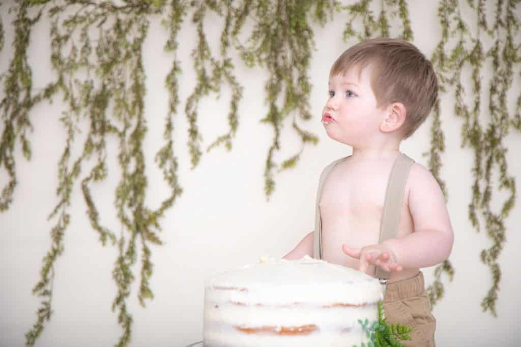 One Year Old Boy in suspenders and tan pants, green garland, no shirt, silly face