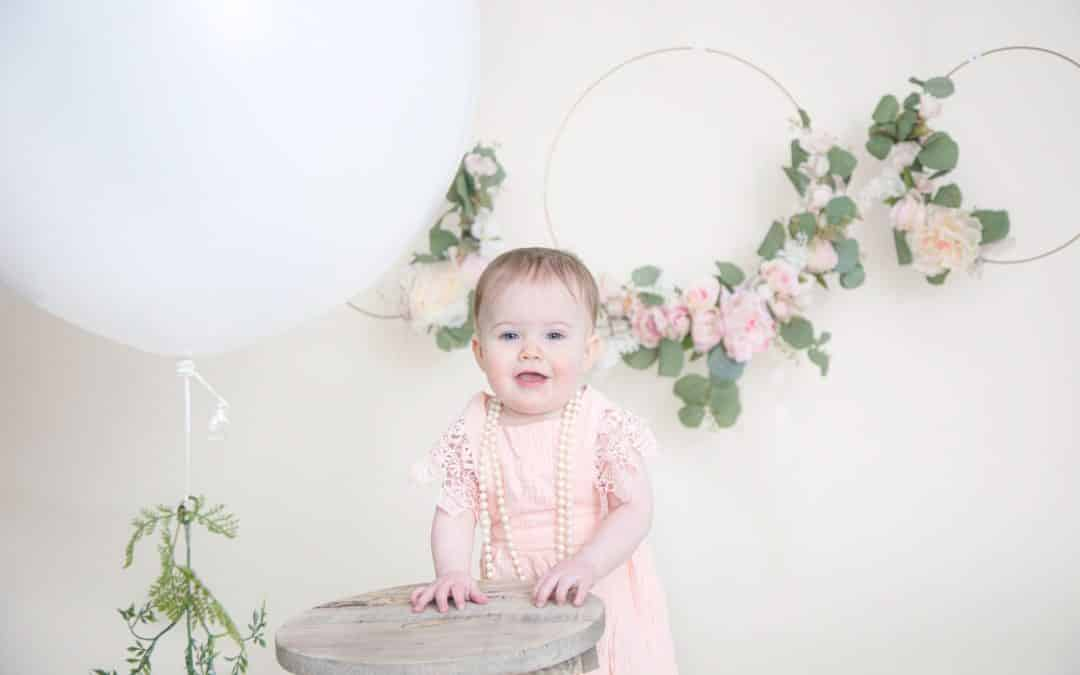one year old in pink dress hands on a wooden stool smiling at the camera