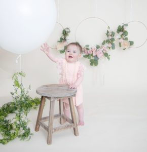 One year girl looking at the camera smiling reaching to touch a large white balloon holding onto the brown stool
