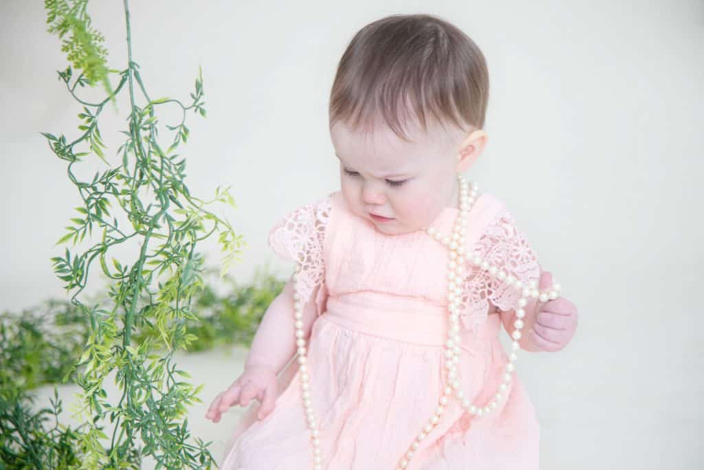 One year girl in pink dress holding pearls looking down