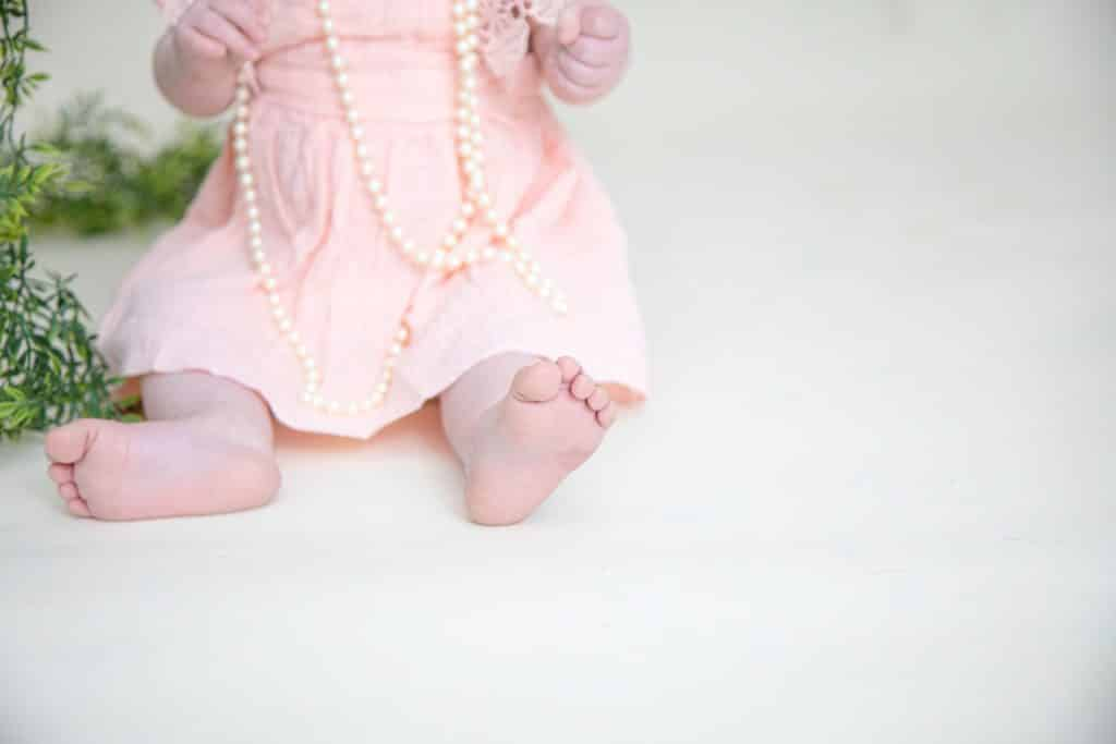 one year girl in pink dress on white background. Picture of her feet