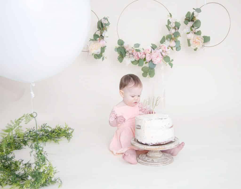 one year girl looking at the cake with a pink dress and white balloon