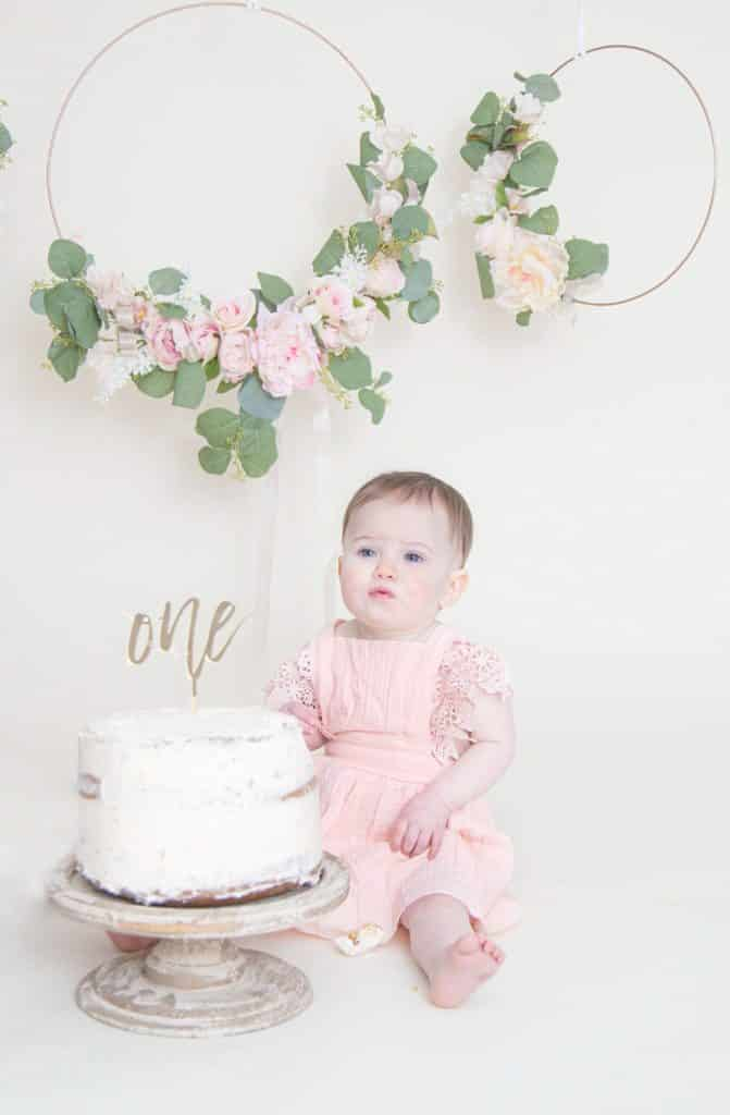 One year girl looking at the camera sitting in front of cake smash with puckered lips