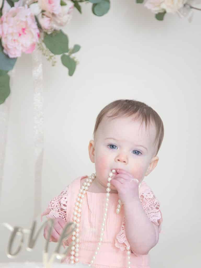 One year girl in pink dress looking at the camera sucking on pearls