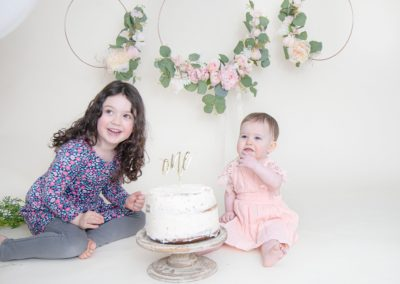 One year old and sister looking at the camera and eating cake