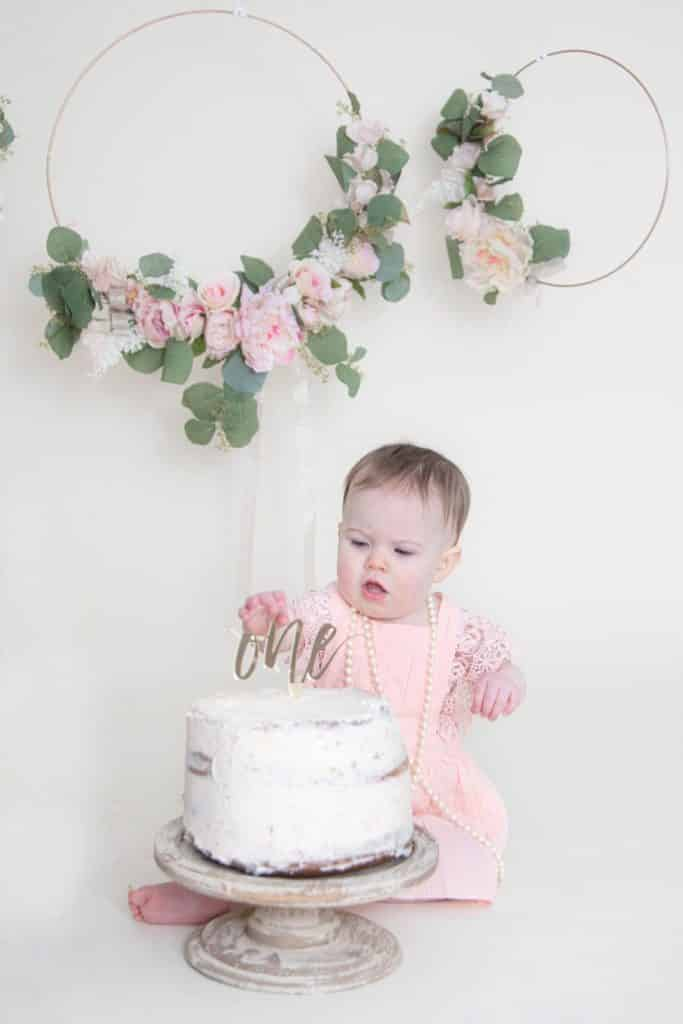 one year old girl sitting in front of her cake looking at the cake with her hand on it
