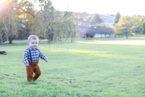 Little brother running in the grass near the augusta, Maine capitol