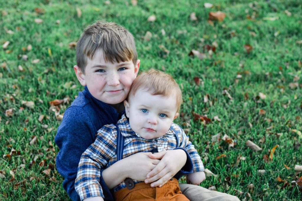 brothers.Big brother holding little brother on his lap sitting pn the grass