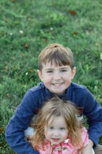 big brother sitting in the grass holding his little sister
