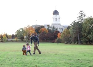 dad chasing his two little kids in the grass near the augusta, MAine captiol