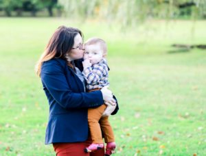 mom kissing her baby boy in the park