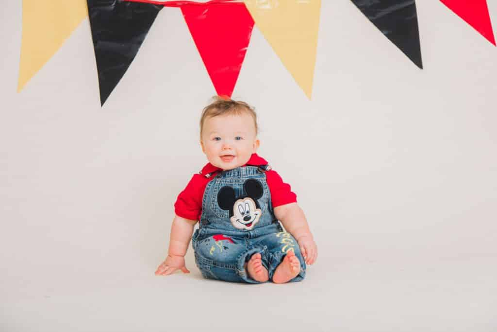 red, white, black banner, one year old smiling at the camera