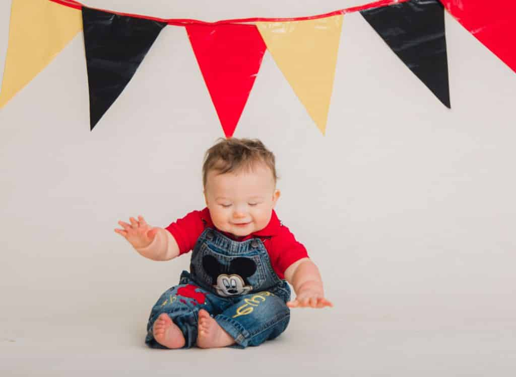 red, black, yellow, banner with one year old laughting