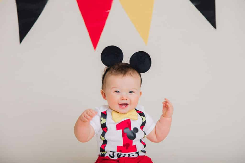 red, yellow, black banner, one year old with mickey mouse ears smiling and looking at the camera with a red one on his shrt