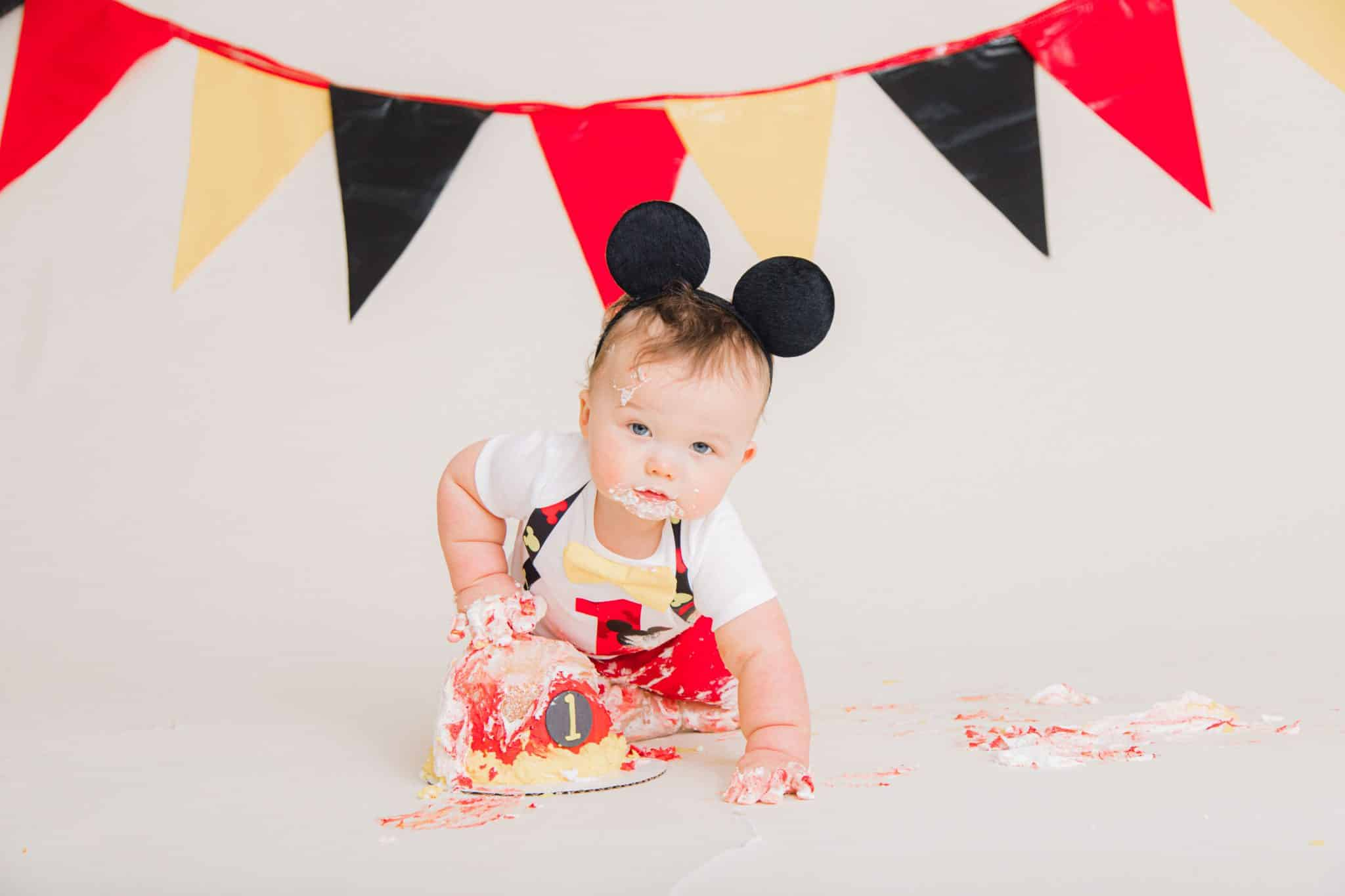 red, yellow, black banner with one year boy, mickey mouse ears, red one on his shirt with a mickey mouse cake