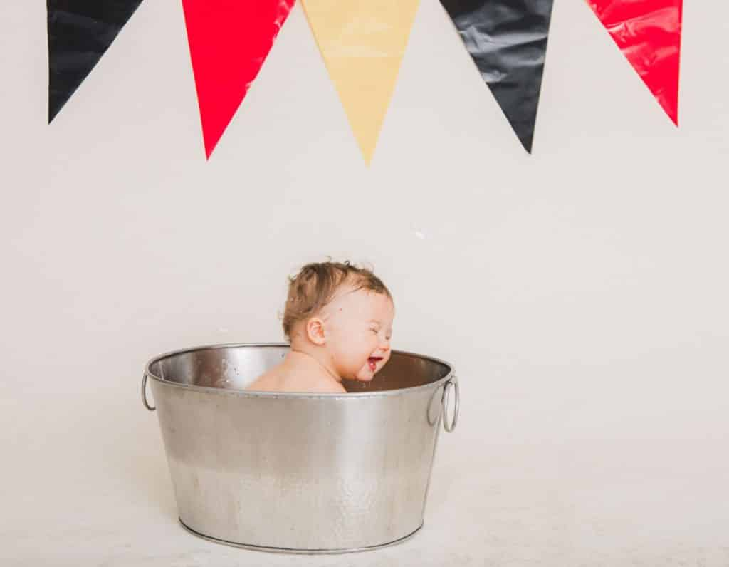 red, yellow, black banner in the background. One year boy in a silver bucket with bubbles smiling