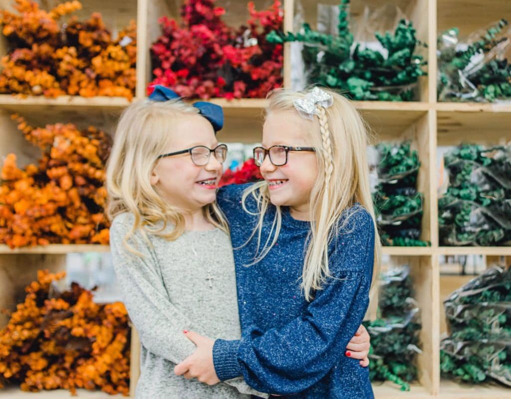 twin blonde girls with glasses holding each other and looking at each other with colors behind them