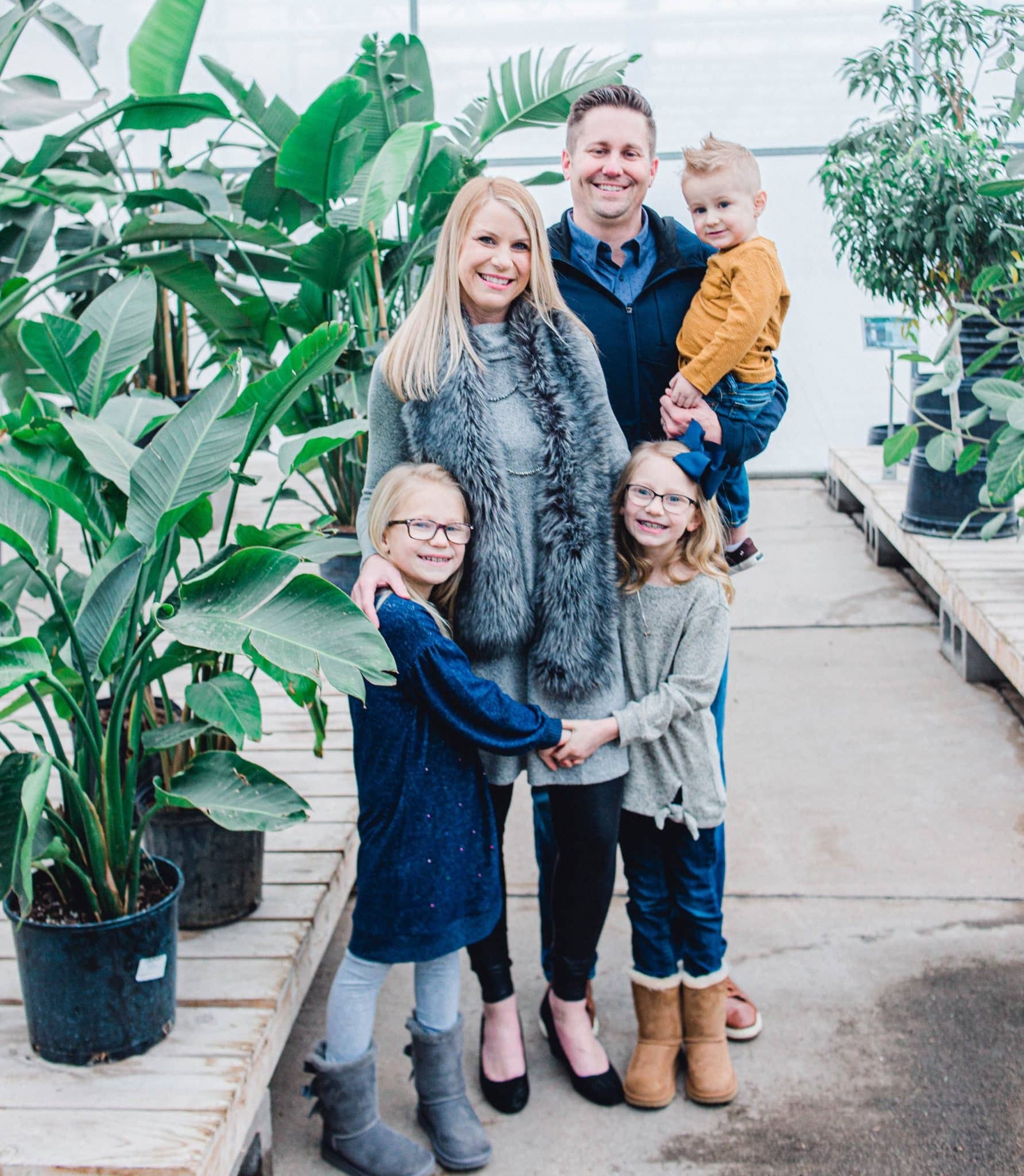 family of 5 looking at camera, in greenhouse