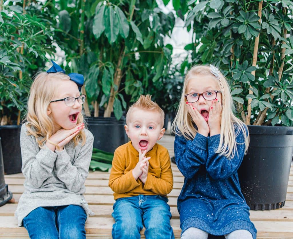 three kids. Two girls and one boy making a silly face in a greenhouse