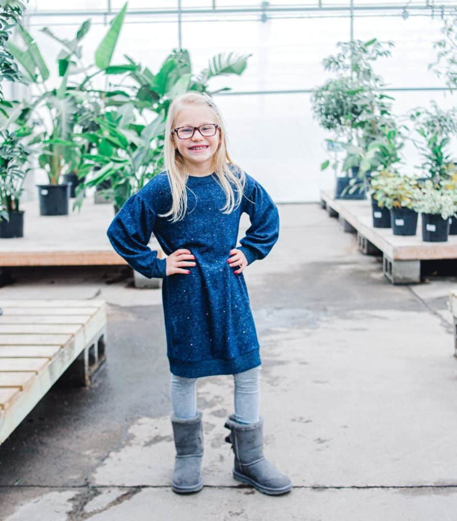 Maine girl in greenhouse looking at the camera