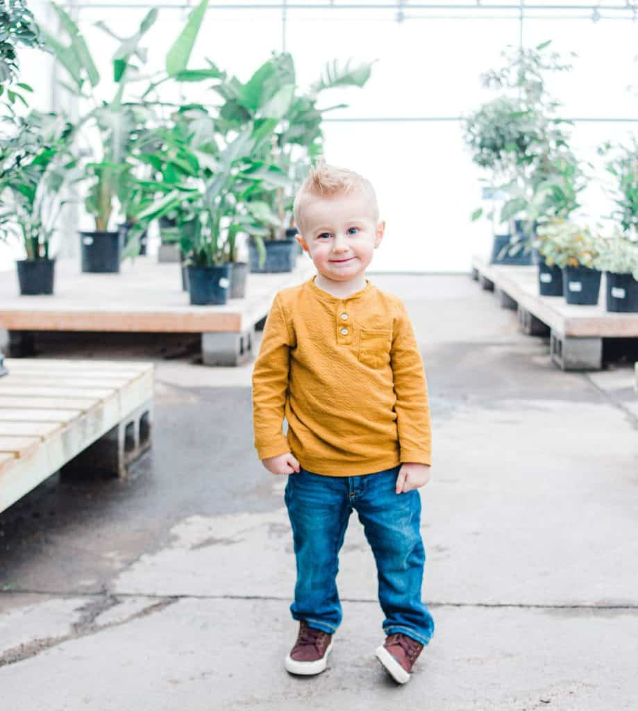Maine toddler standing in greenhouse looking at the camera