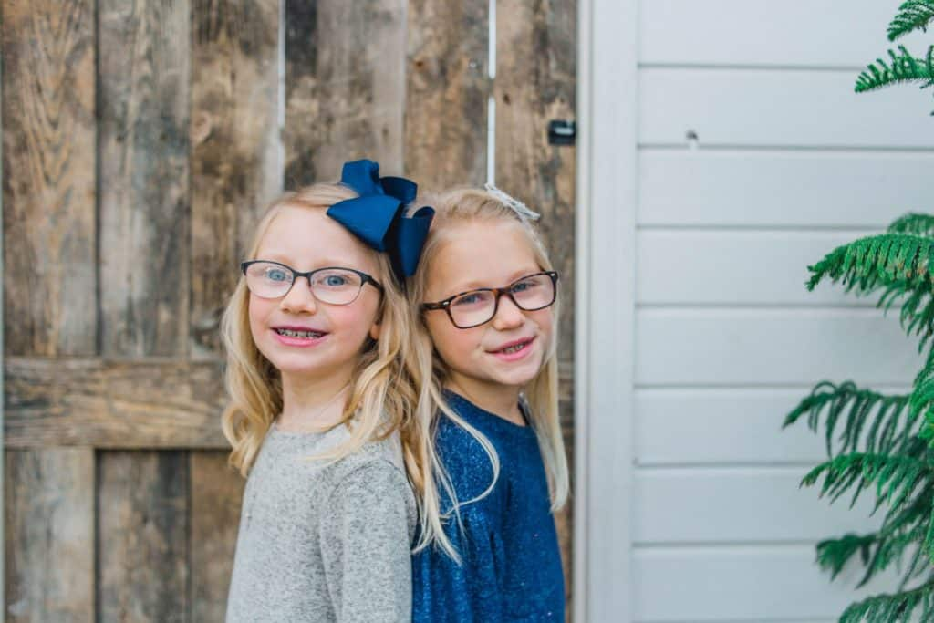 sisters back-to-back looking at the camera in front of a barn door
