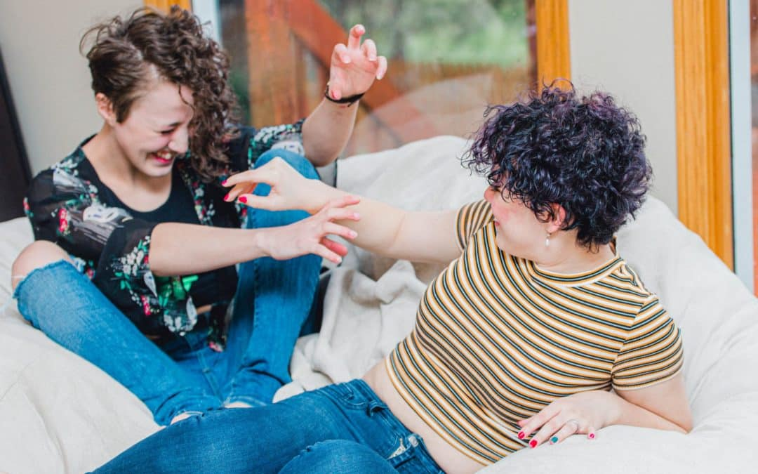 two teenage girls sitting on a bean bag laughing