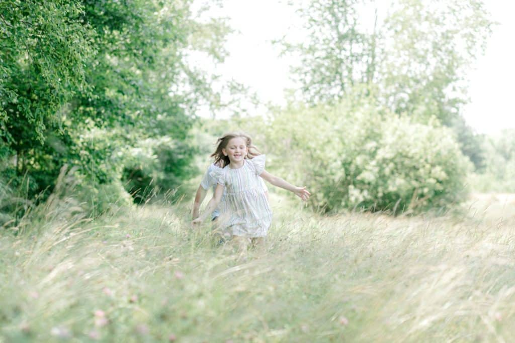little girl running towards the camera in the tall grass