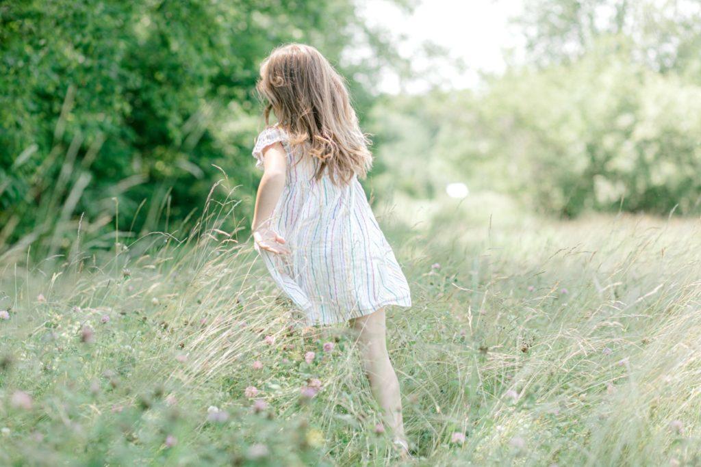 little girl running through tall grass