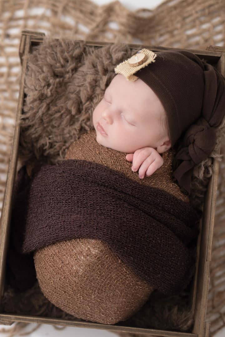 baby in a basket asleep in maine photo studio