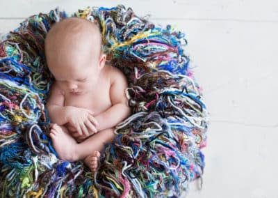 brunswick maine newborn photographer gets a shot of a newborn baby sleeping curled up in a colorful basket