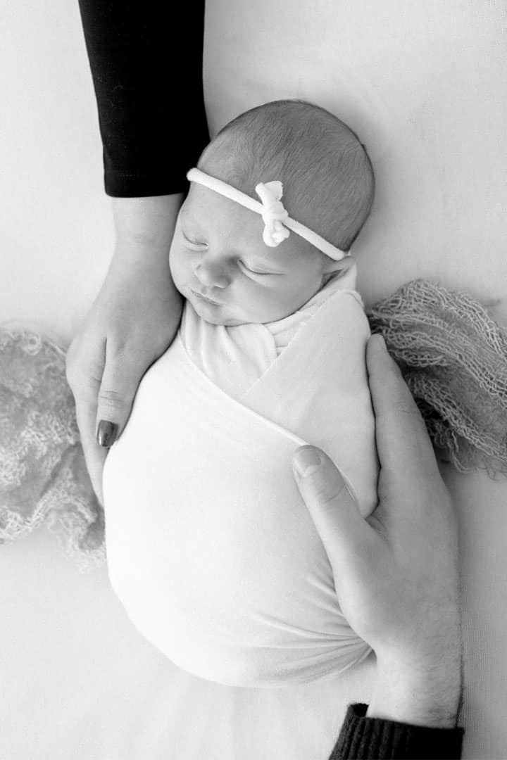 newborn picture caressed by two hands