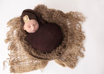 maine newborn sleeping wrapped in a blanket